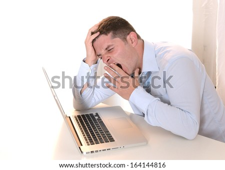 Tired and Overworked Businessman yawning sleeping at Work - stock photo