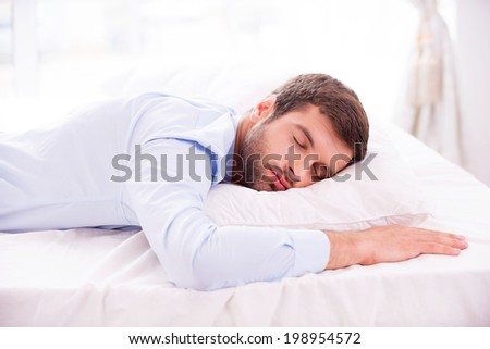 Tired and overworked. Handsome young man in shirt sleeping in bed  - stock photo