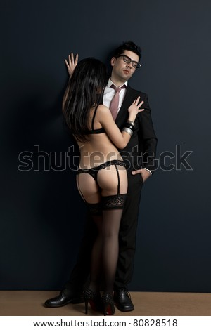 Tired and upset businessman with a sexy young woman in lingerie. Concept about work and pleasure - stock photo