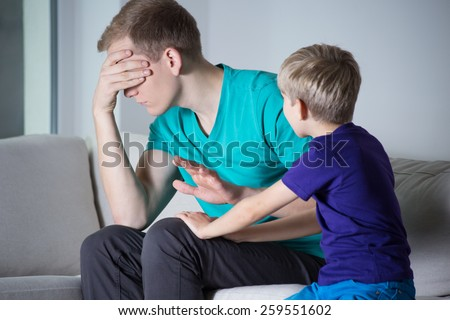 Tired angry father and his energetic son - stock photo