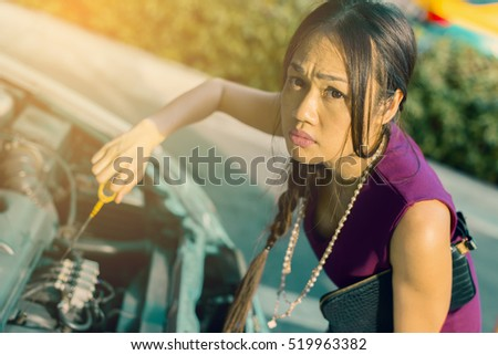 Tired Asian businesswoman broken car on a working day and opened the hood broken car on the side see engines that are damaged or not.
