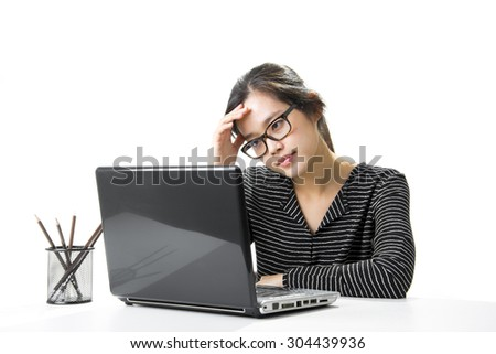 Tired asian businesswoman working at computer in her office - stock photo