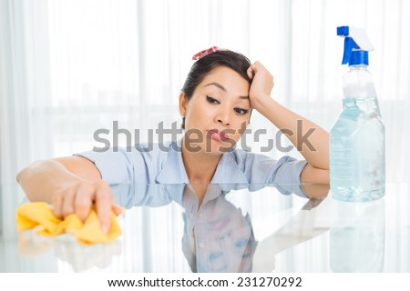 Tired Asian housewife wiping a glass table - stock photo