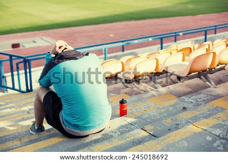 tired athlete after failing resting with a bottle of water sitting on the stairs at stadium - stock photo