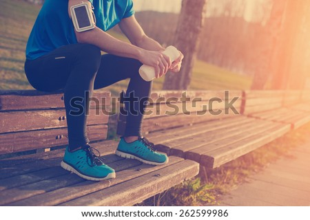 Tired athlete resting on the bench in park with bottle of water (intentional sun glare and vintage color) - stock photo