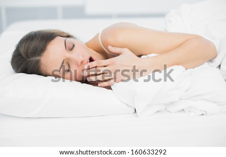 Tired attractive woman yawning while lying on her bed in bright bedroom - stock photo