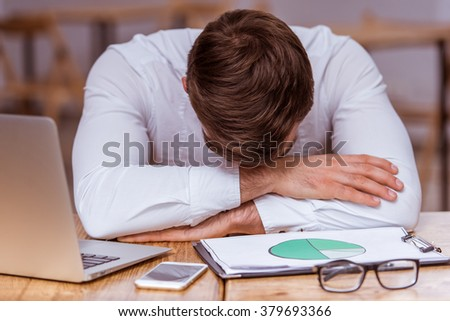 Tired attractive young businessman in white classical shirt leaning on the table after working with a laptop and documents in the cafe - stock photo