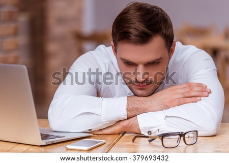 Tired attractive young businessman in white classical shirt leaning on the table after working with a laptop and documents in the cafe