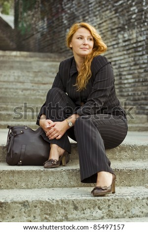 tired beautiful redhead business woman in suit sitting on stairs - stock photo