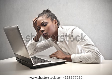 Tired black woman in front of a computer - stock photo