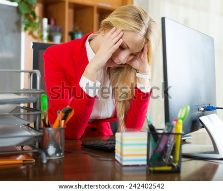 tired blonde woman with office work sitting at the computer - stock photo