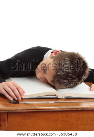 Tired, bored, weary, stressed school student at desk. - stock photo