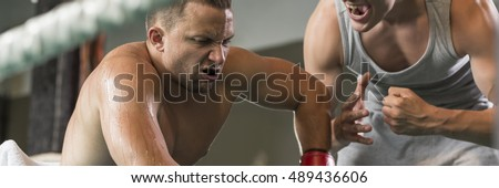 Tired boxer is sitting and his trainer motivates him to work