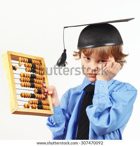 Tired boy in academic hat with old abacus on a white background - stock photo