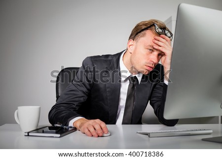 Tired business man at the office  - stock photo