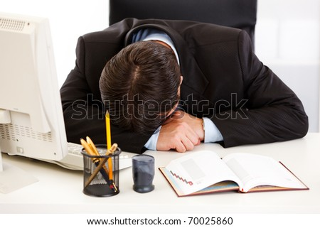 Tired business man sleeping at  desk in  office - stock photo