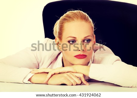 Tired business woman sitting behind the desk - stock photo