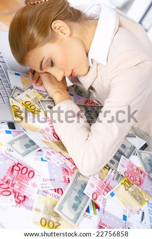 Tired business woman sleeping on table with lots of cash on it - stock photo