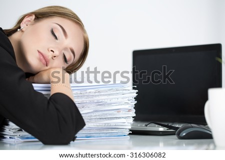 Tired business woman slleeping on heap of papers at her working place. Overwork, working overtime and stress at work concept. - stock photo