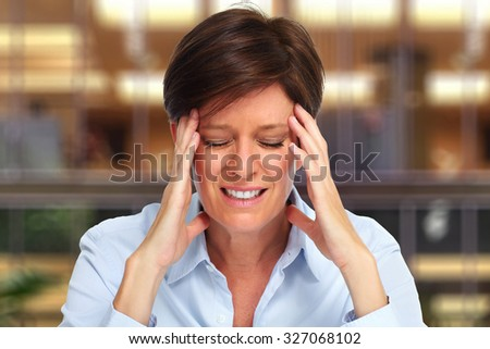 Tired business woman with headache migraine over house background - stock photo