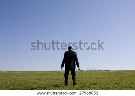 tired businessman after walking in the field - stock photo