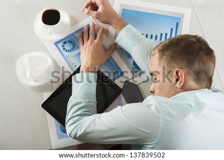 Tired businessman is sleeping in his office - stock photo