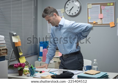 Tired businessman leaning to his desk and touching his painful lower back. - stock photo