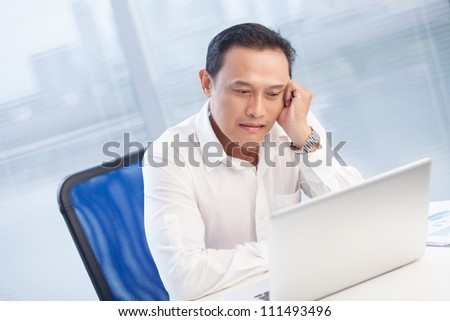 Tired businessman sitting at the table and looking at laptop at office - stock photo