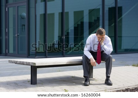 Tired businessman sitting on a bench in front of an office building - stock photo