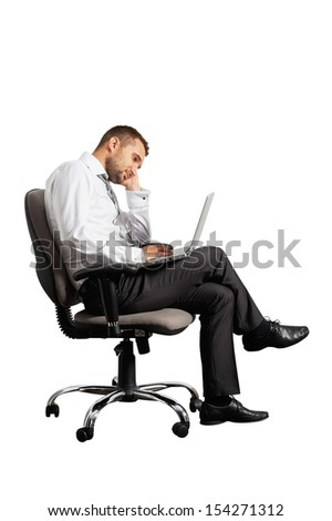 tired businessman sitting on office chair and looking at laptop