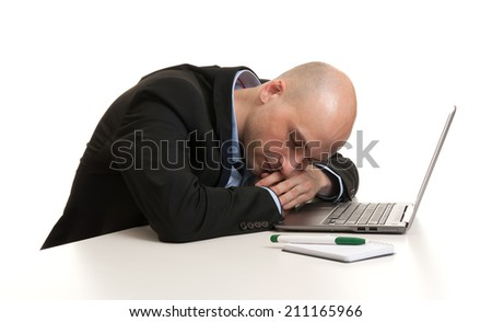 Tired businessman sleeping at work place - isolated over white - stock photo