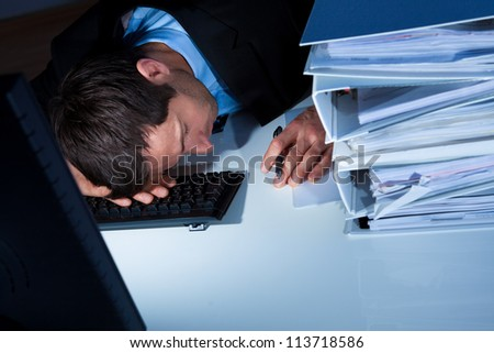 Tired Businessman Sleeping At Workplace In The Office - stock photo