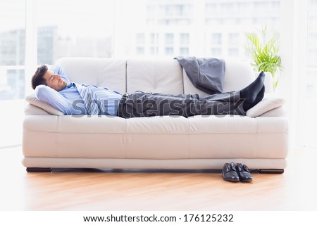 Tired businessman sleeping on a sofa in the office - stock photo