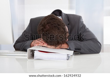 Tired Businessman Sleeping Over Folder At Office - stock photo