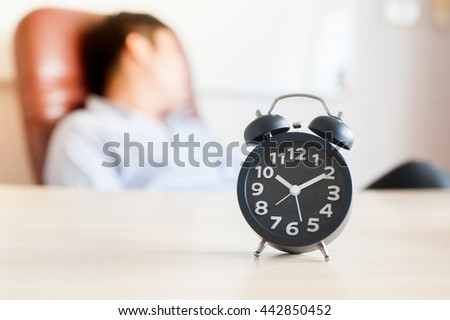 Tired businessman sleeping with laptop and clock on wood table   - stock photo