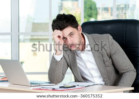 Tired Businessman. Successful confident businessman sitting in office at the table and working on a laptop while young businessman in formal attire thinking on the problem - stock photo