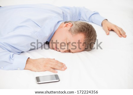 Tired businessman. Top view of tired grey hair man in blue shirt sleeping on bed  - stock photo