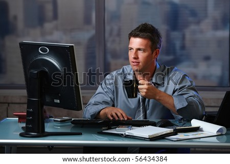 Tired businessman working late doing overtime in office at night drinking coffee to go on. - stock photo