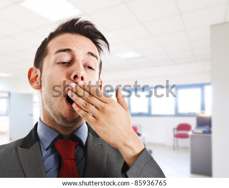 Tired businessman yawning - stock photo