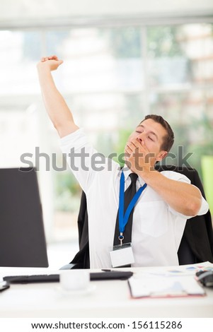 tired businessman yawning in office