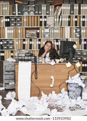 Tired Businesswoman in a messy office - stock photo