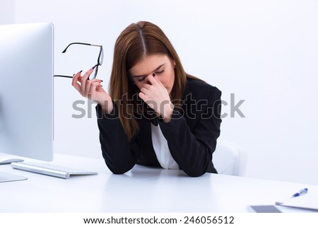 Tired businesswoman rubbing her eyes in office - stock photo