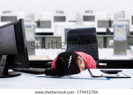 Tired businesswoman sleeping on her desk in the office