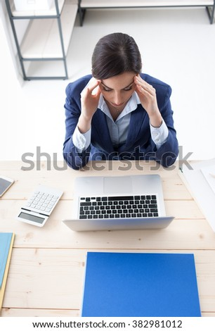Tired businesswoman with head in hands, working in the office and having an headache, stressful life concept - stock photo