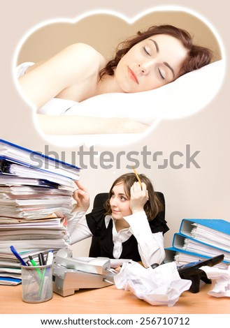 Tired businesswoman with telephones and pen in her mouth sitting and dreaming of a sleep - stock photo
