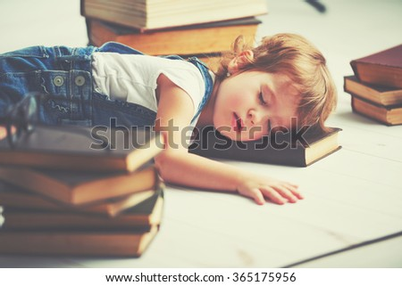 tired child little girl fell asleep for books - stock photo