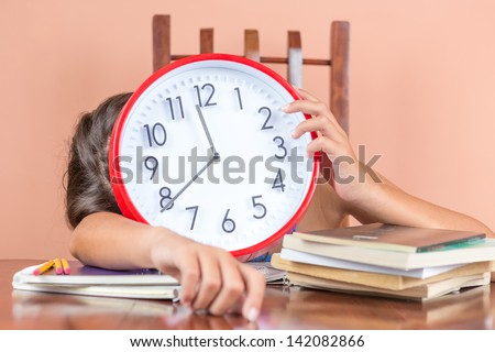 Tired child sleeping on a desk full of books and holding a clock in place of her face to symbolize tiredness after studying too much - stock photo