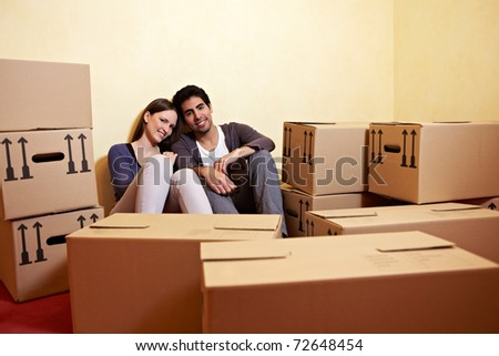 Tired couple sitting between many boxes in their new home - stock photo