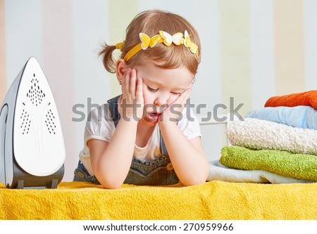tired   cute little baby girl housewife iron clothes iron, is engaged in domestic work - stock photo