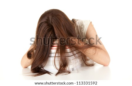 tired, depressed  female student leaning on the stack of books, white background - stock photo